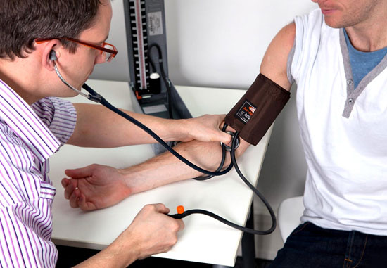 кардиолог измеряет пациенту давление