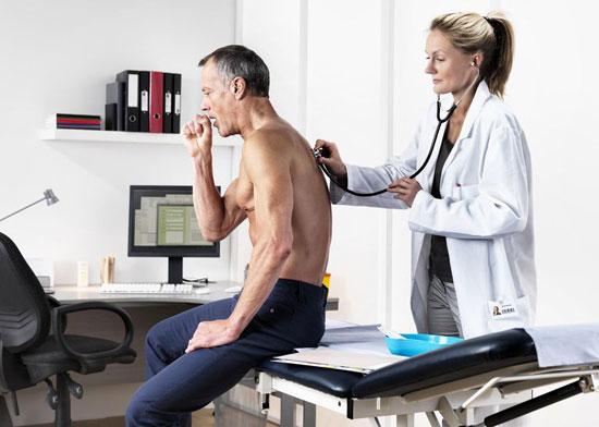 терапевт с помощью стетоскопа прослушивает легкие на наличие хрипов