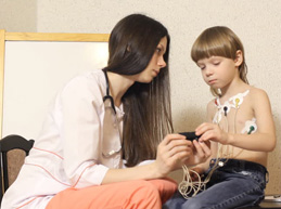 девушка, врач-кардиолог, рассказывает мальчику про аппарат суточного мониторинга ЭКГ